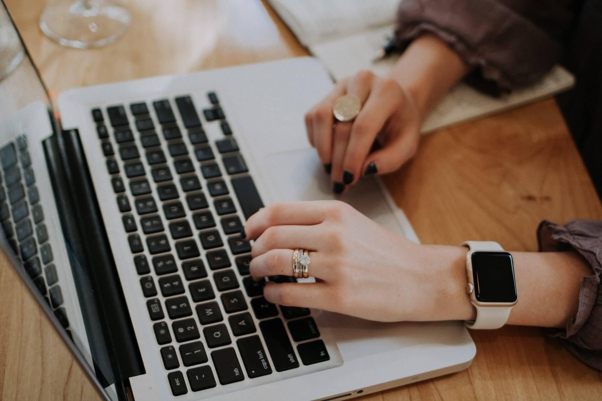 femme qui tape sur le clavier d'un ordinateur portable